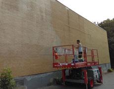 Photo d'une personne en train de réaliser une murale sur un mur d'immeuble